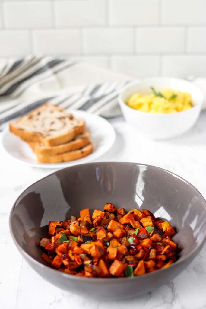 A grey bowl of the home fries on a  white marble board, in the background blurred scrambled egg and toast.