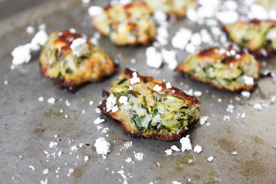 greek zucchini tots on a baking sheet with scattered feta cheese.