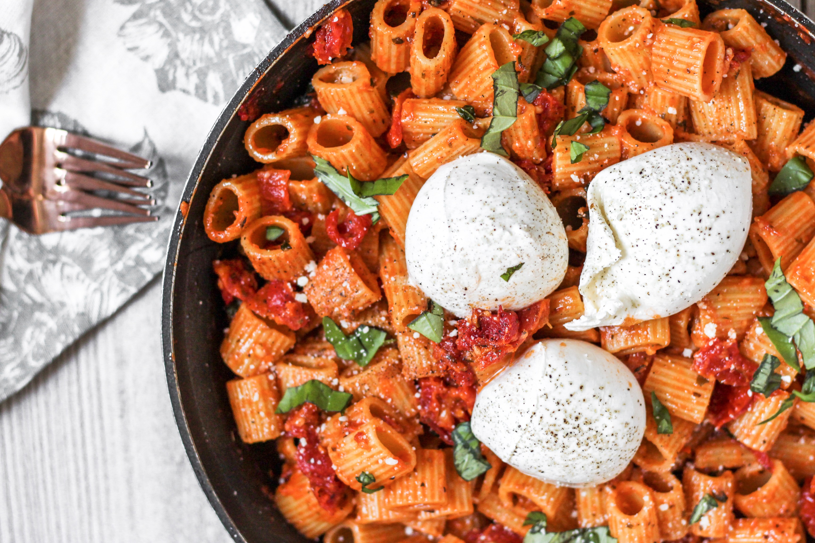 overhead shot of the pasta in a pan with 3 balls of Burrata, a floral linen napkin and 2 forks.