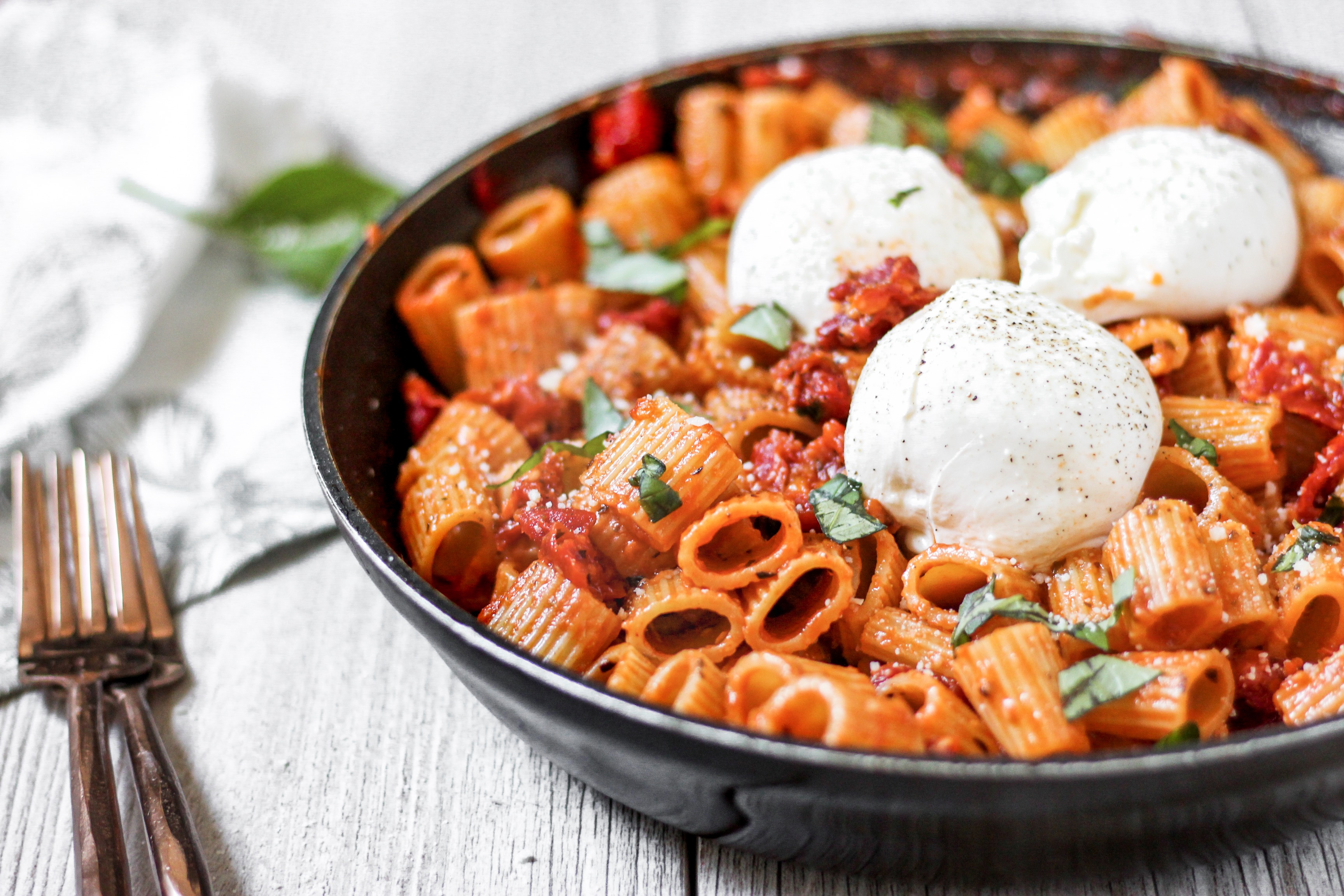 pasta in the pan with 3 balls of Burrata and 2 forks.