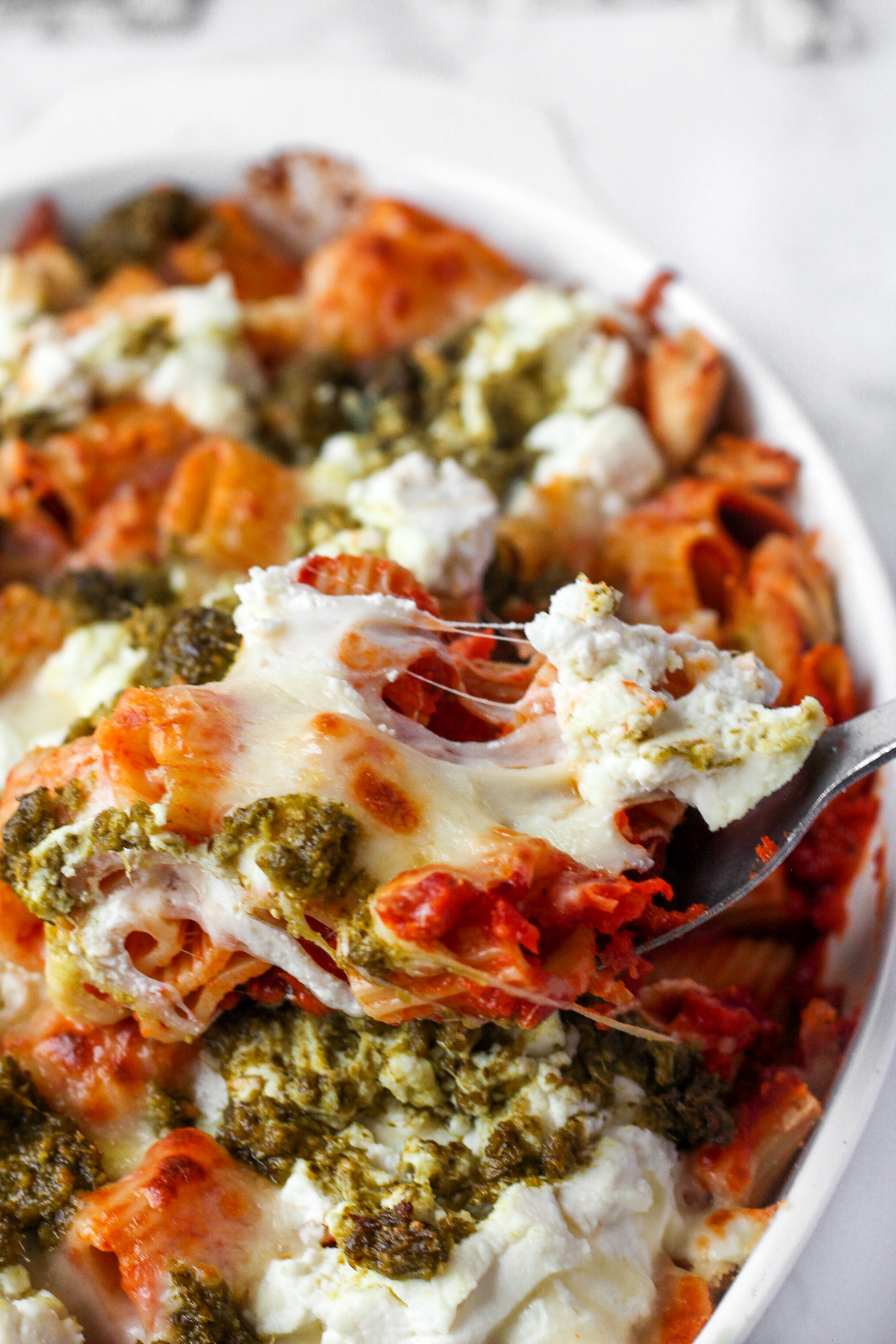 spooning the chicken pesto pasta bake from the casserole dish
