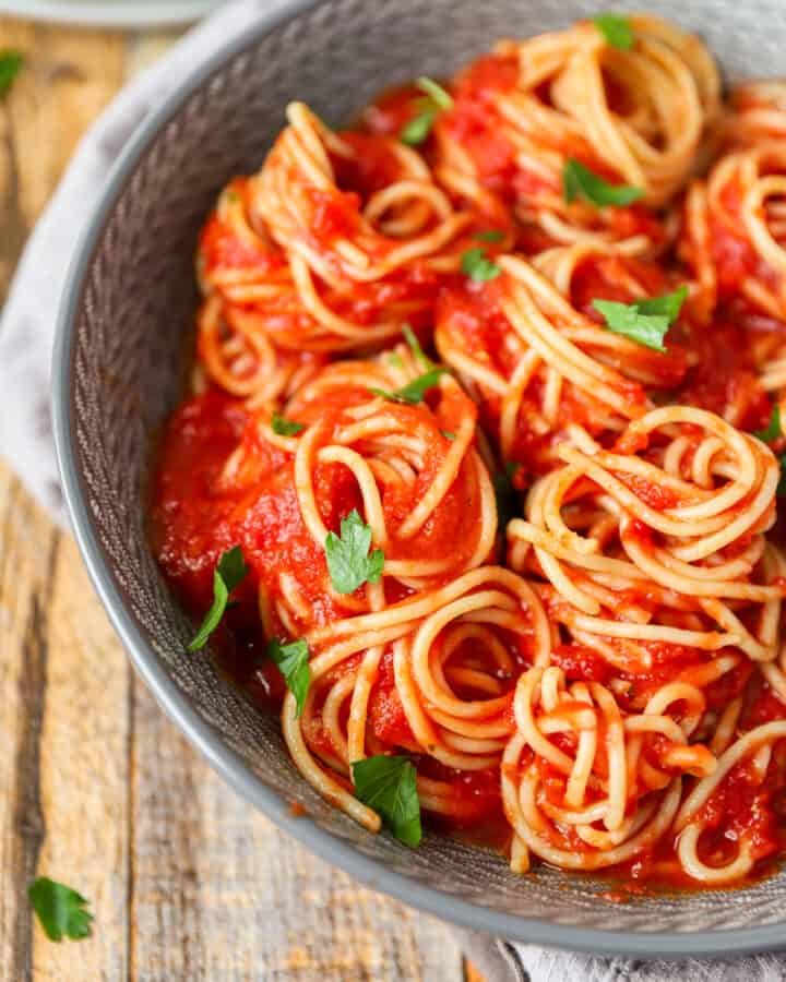 spaghetti with red sauce in a grey bowl