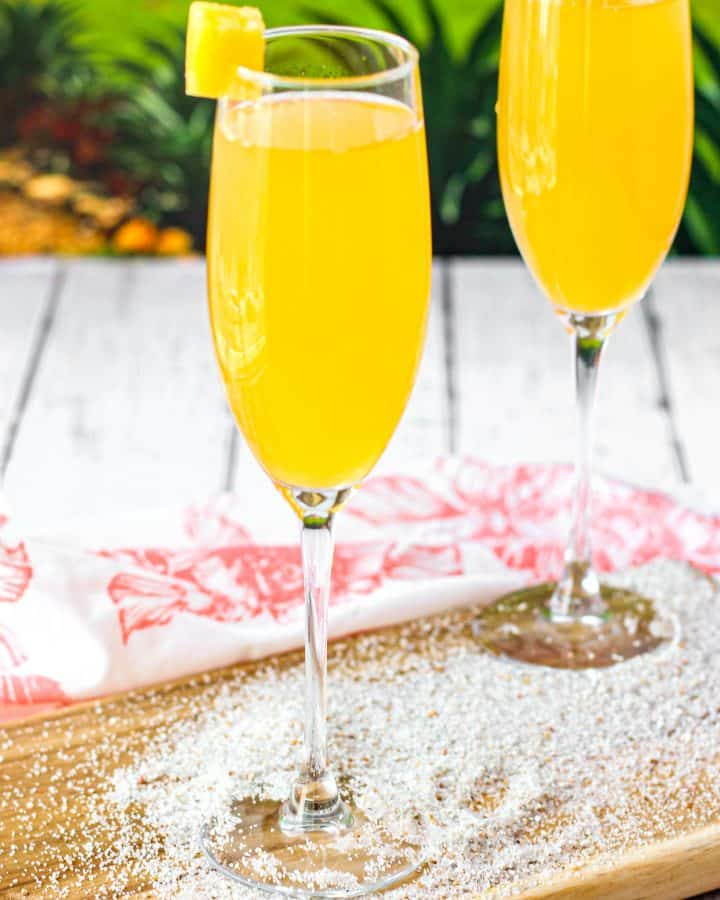 Two peach mimosas on a wood board with sand and a green background.