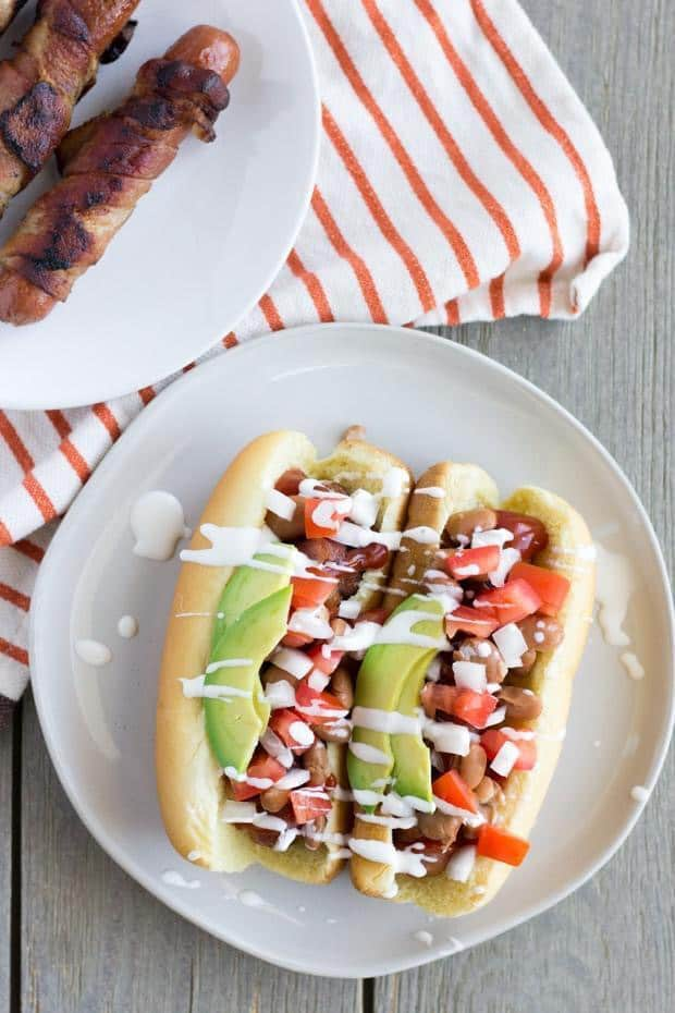 Overhead shot of two of the hot dogs on an off-white plate. Hot dogs are topped with tomatoes, onions, avocado and a white sauce. To the back left, a plate of the grilled hot dogs and an orange stripped napkin.