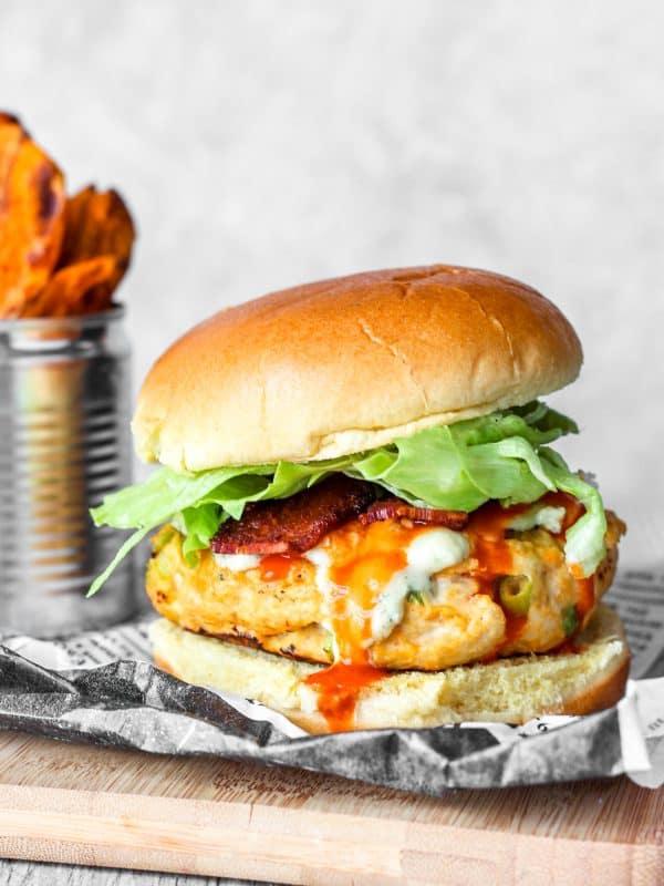buffalo chicken burger on wood board with sweet potato fries