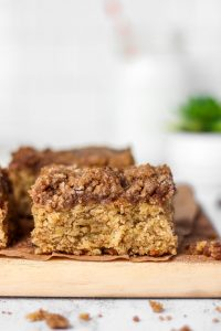 a slice of banana coffee cake on a wood board on a marble surface. Crumbs in the foreground and a succulent in the back.