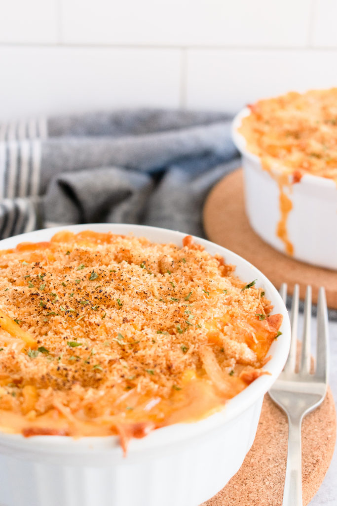 cheesy mac and cheese in a white dish with a fork.