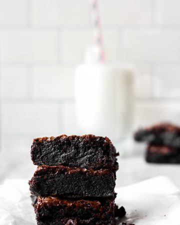 A stack of 3 brownies on wax paper on a white surface, a glass of milk in the background.
