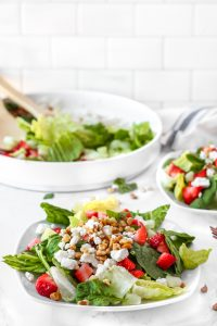 A plate of the strawberry goat cheese salad on a white marbel surface. Blurred in the background is another plate of the salad and the large bowl of salad.