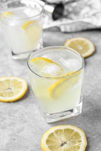 A limoncello vodka cocktail on a concrete surface with lemon slices.