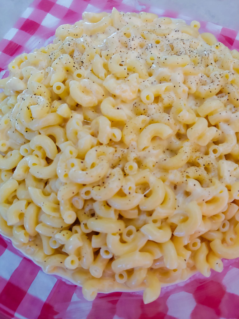 creamy mac and cheese in a red and white checkered bowl.