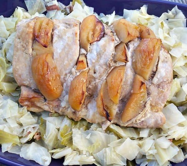 overhead shot of the apple stuffed pork tenderloin on a bed of cabbage.