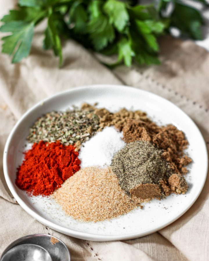 sazon spices on a white plate with parsley in the background.
