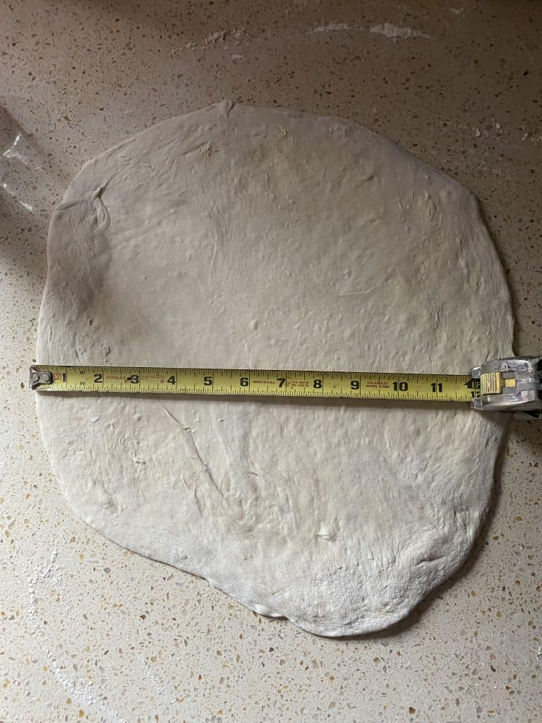 "raw dough on a countertop rolled into a 12"" circle with a tape measure showing it's 12"" wide."