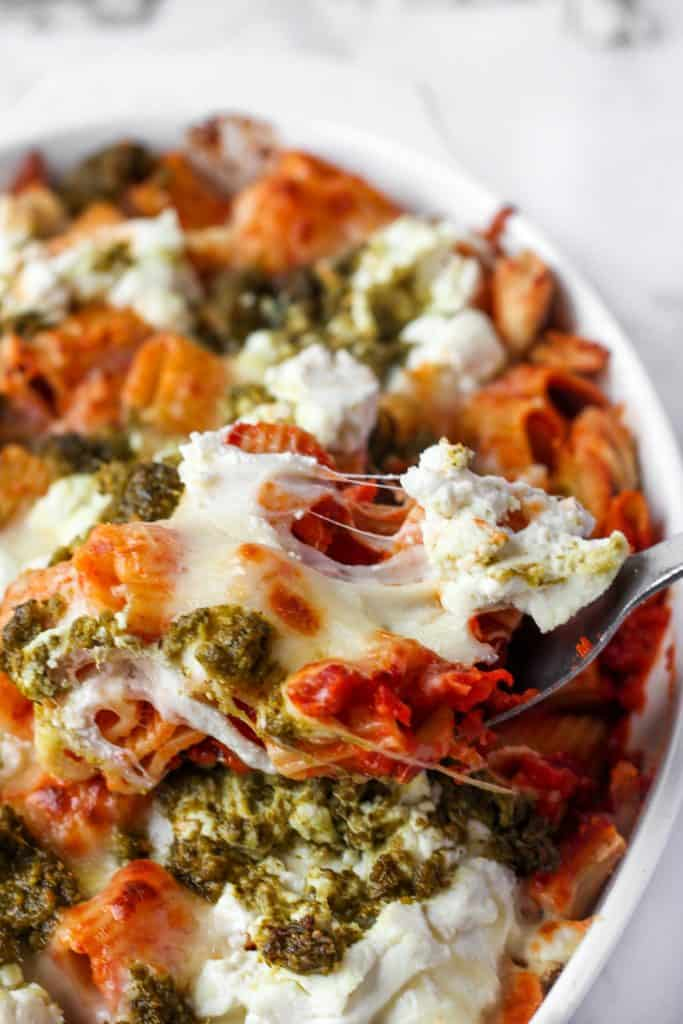 chicken pesto pasta bake with a spoon scooping, in a white baking dish.