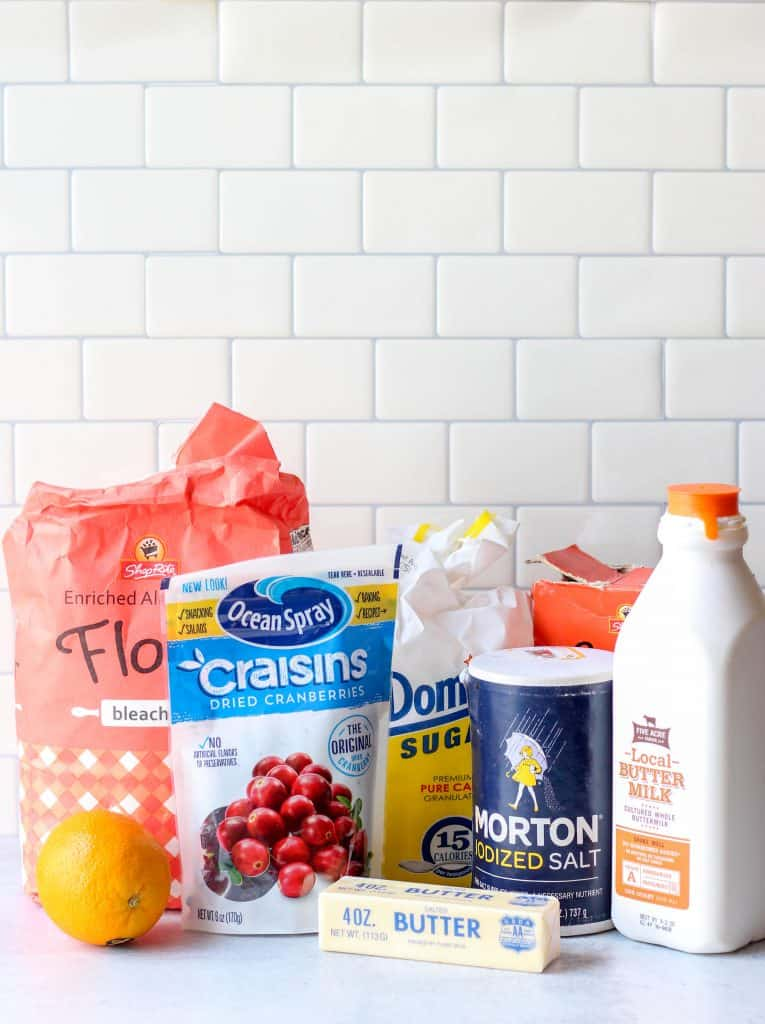 ingredients, a bag of flour, a bag of dried cranberries, a bag of sugar, a stick of butter, an orange, a box of baking soda, salt, and buttermilk.