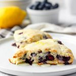 two lemon blueberry scones on a white round plate.