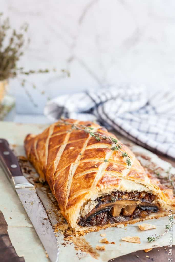 mushroom wellington with a knife on parchment paper.