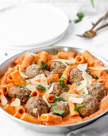 A silver pan with the rigatoni and meatballs on a white marble surface.