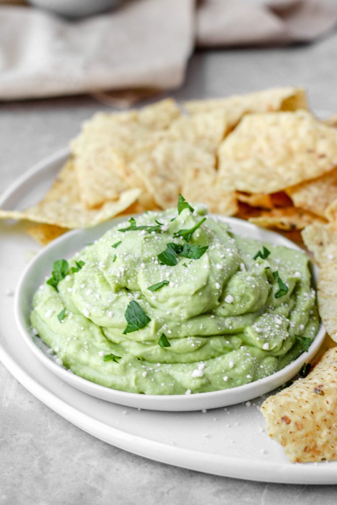 whipped avocado on a white plate with chips.