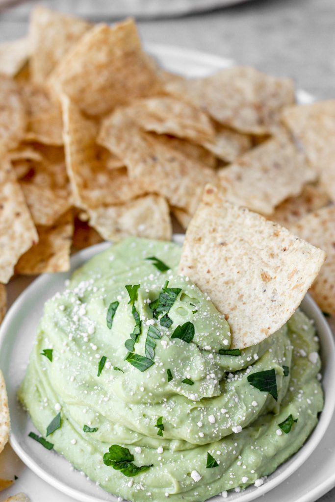 whipped avocado butter fruit on a white plate with chips.