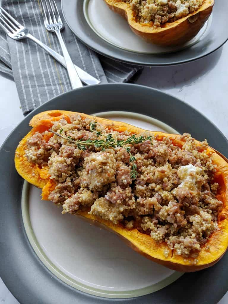overhead view of the stuffed butternut squash with a napkin and two forks.