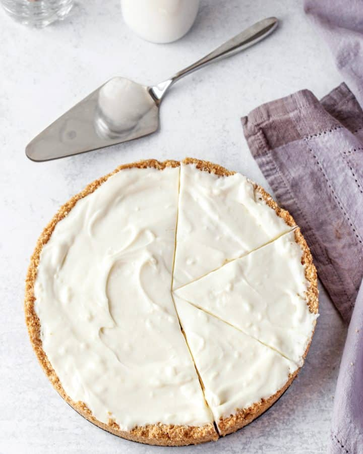 overhead shot of the no bake coconut cheesecake with a pie server and a napkin on a cement surface.