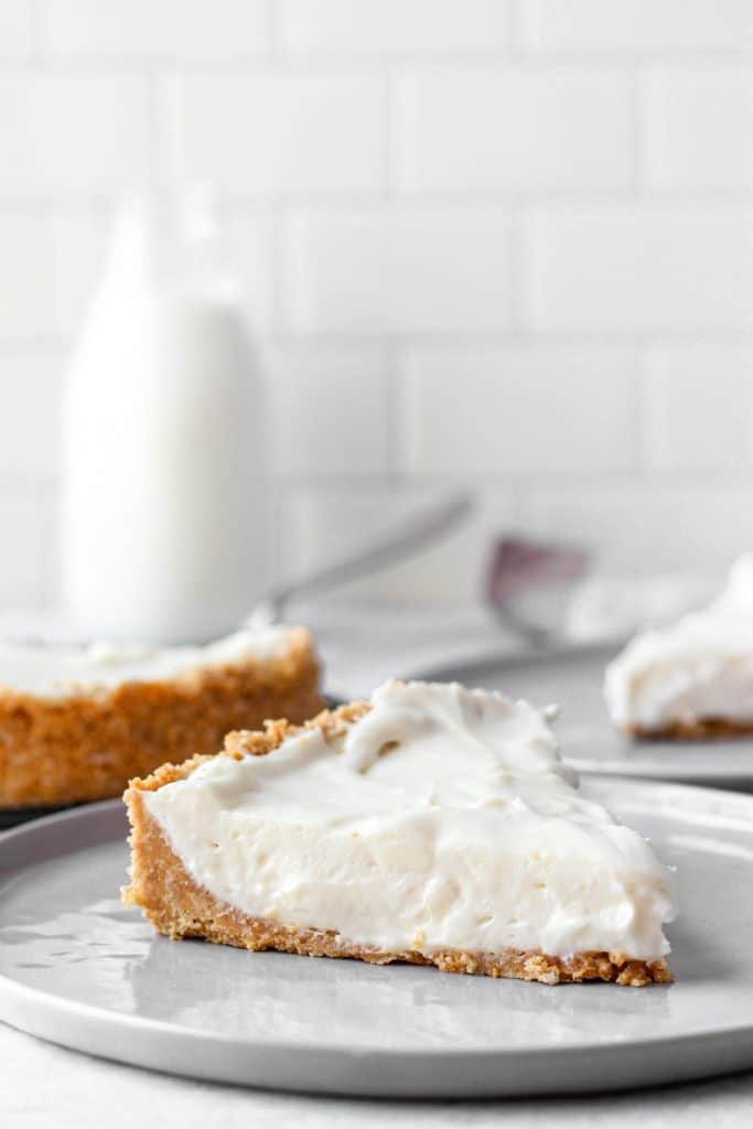 a slice of the cheesecake on a grey plate. In the back the whole cheesecake, another slice on a plate, and a glass of milk.