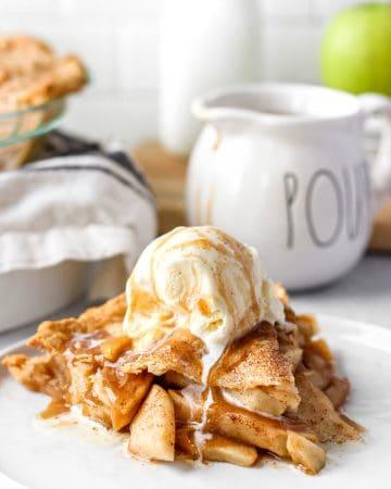 apple pie slice with the sauce drizzle and vanilla ice cream