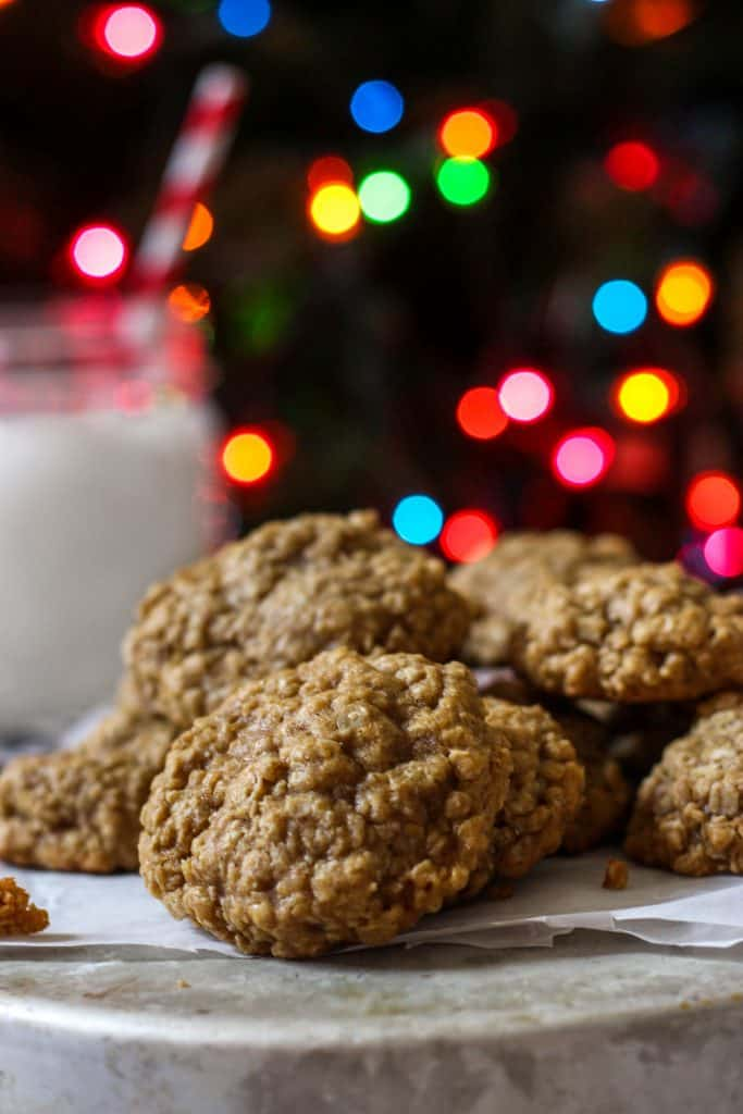 brown butter oatmeal cookies with a background of evergreen and christmas lights and a glass of milk.