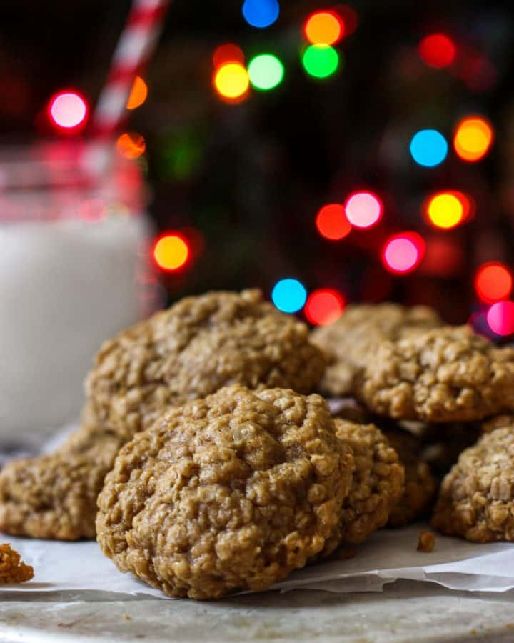 brown butter oatmeal cookies on a silver tin with christmas lights behind