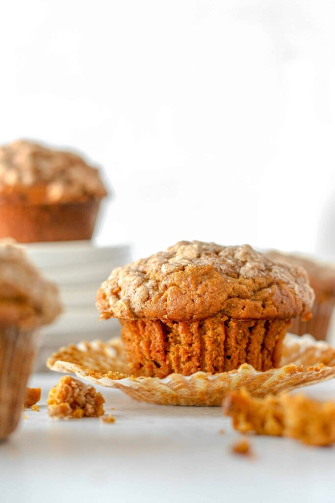 a pumpkin muffin with the wrapper unwrapped...a few stacked plates in the background with a muffin on top.