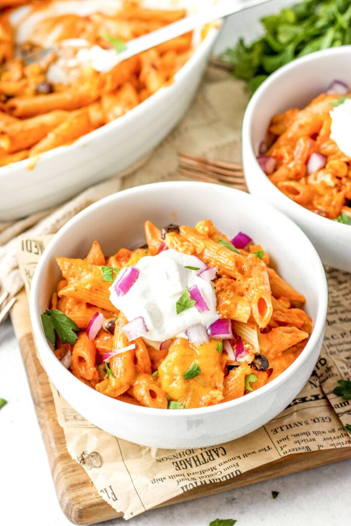fajita pasta in a white round bowl topped with sour cream and diced red onions.
