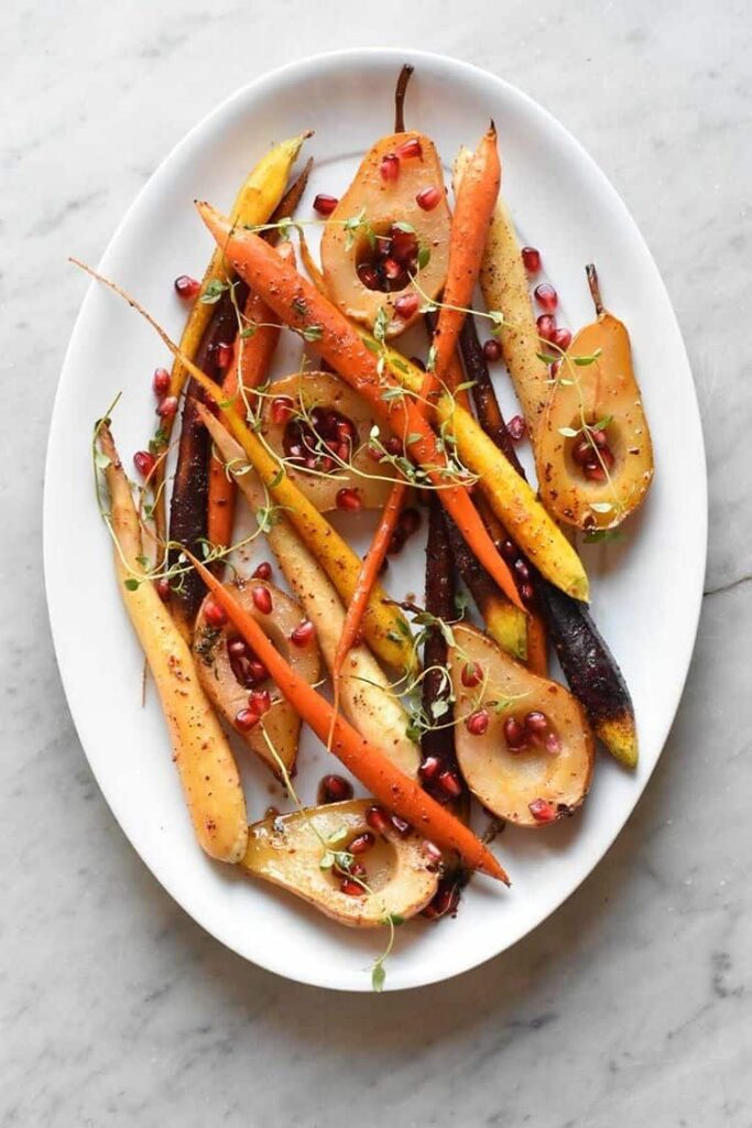 overhead shot of a platter with the carrots, pears, and pomegranate seeds.