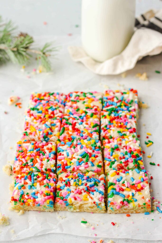 45 degree angle shot of a large rectangle of the sliced cookies on parchment paper, sprinkles everywhere, milk and evergreen in the background.