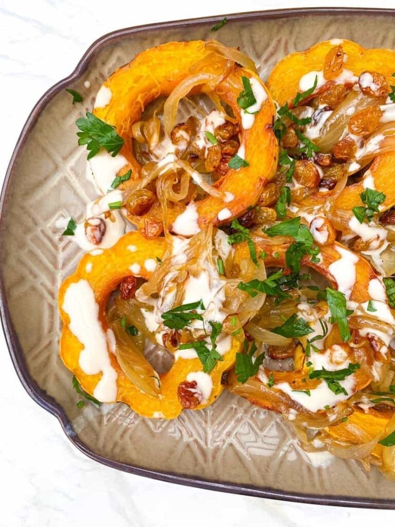 overhead shot of delicata squash, sliced, with a tahini dressing.