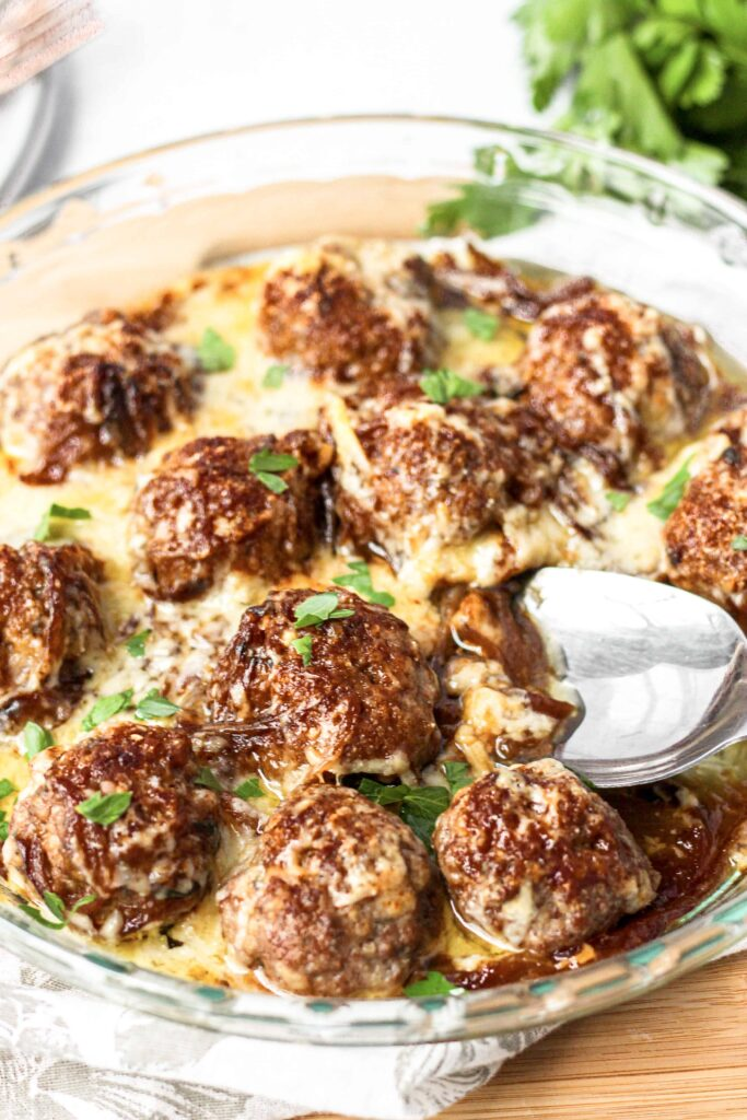 the french onion meatballs in a glass circular baking dish with a silver spoon scooping.
