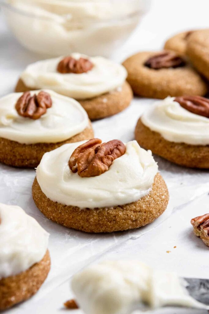 molasses cookies topped with frosting and a pecan.