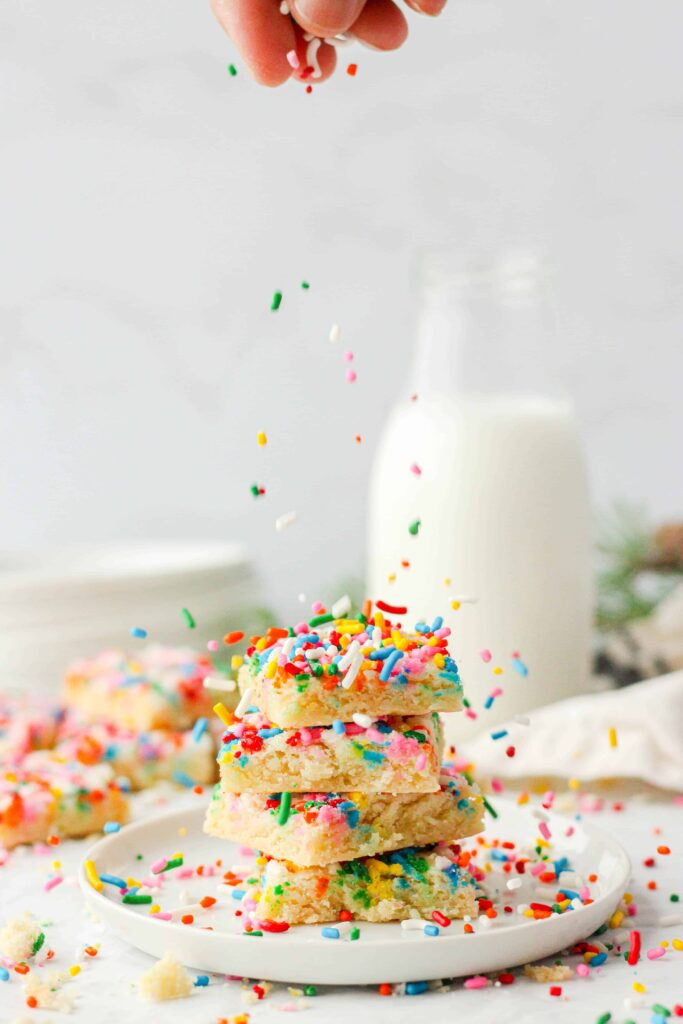 shot of 4 stacked cookies with a hand sprinkling sprinkles. Milk, plates, evergreen and a beige linen in the back.
