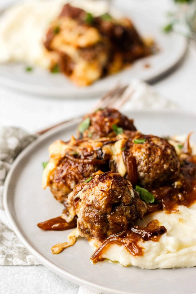 4 meatballs on a grey round plate with mashed potatoes.