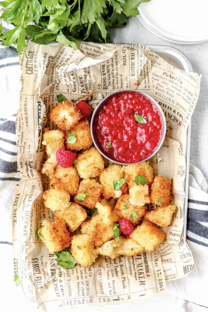 overhead shot of the fried brie bites in a platter with the raspberry sauce, on beige newsprint paper, and a blue striped linen napkin beneath,