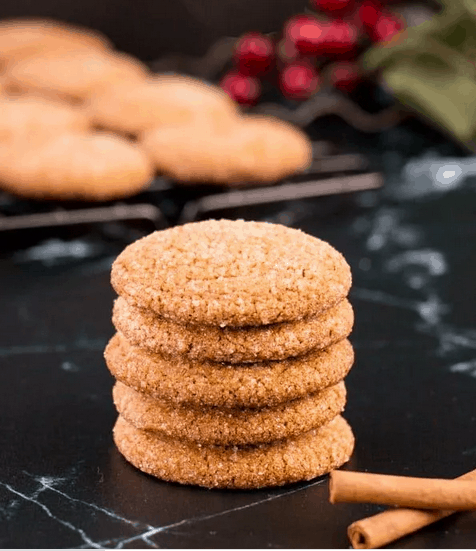 a stack of 5 gingersnaps on a black marble surface. More cookies in the background, 2 cinnamon sticks in the foreground.