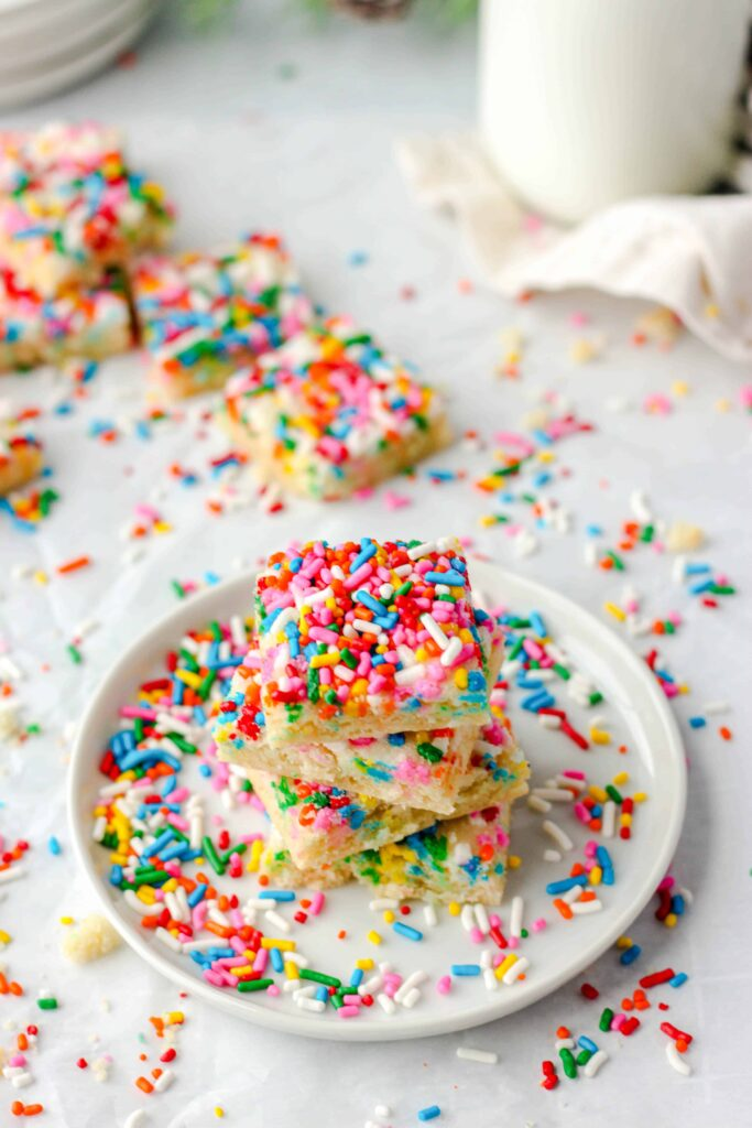 shot taken at 45 degree angle of a stack of  4 square sugar cookies on a round white plate, sprinkles everywhere, some cookies in the background.