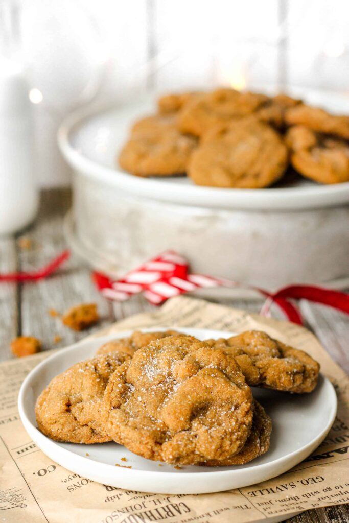 styled photo of the cookies. Foreground: a white round plate with several cookies, plate is on brown printed paper. A red ribbon sprawled in the back, with a larger plate of more cookies.