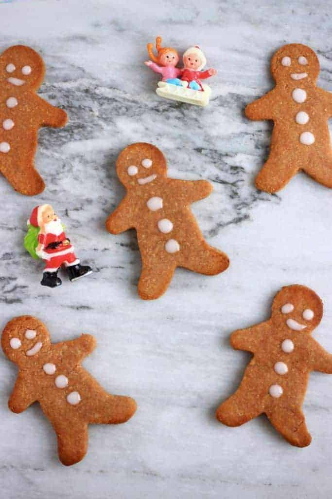 overhead shot of decorated gingerbread men on a white marble surface.