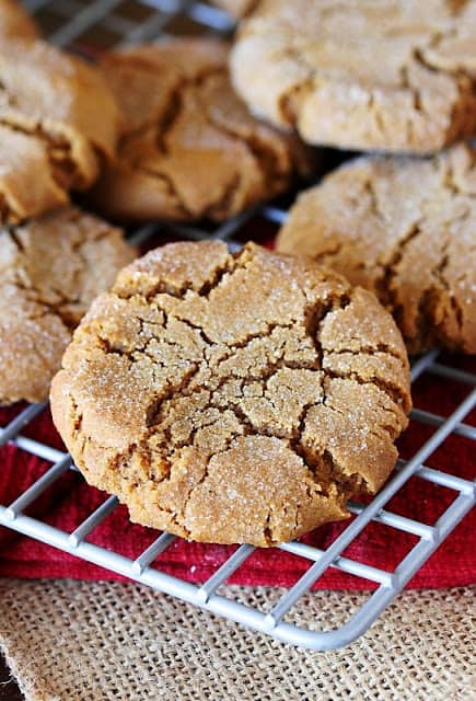 molasses cookie on a cooling rack on red and beige linens.