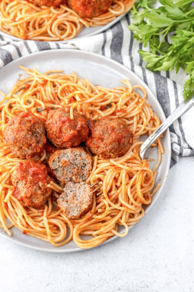 easy baked meatballs on a plate of spaghetti, one of the meatballs cut open to show the interior texture.