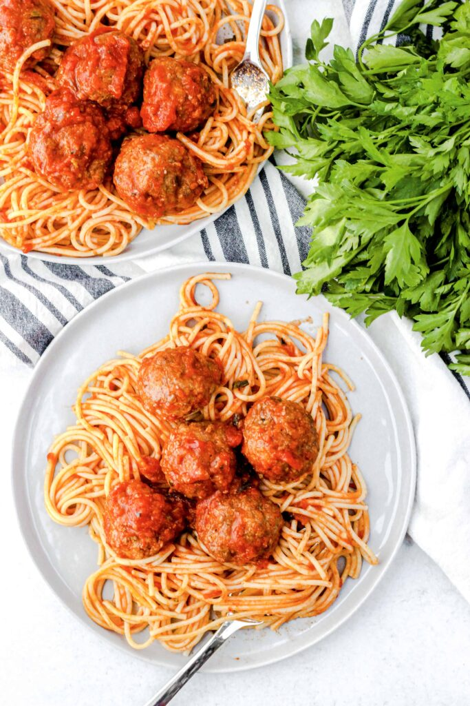 overhead shot of spaghetti and meatballs with a fork and parsley off to the side.