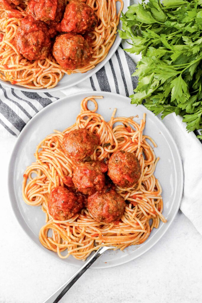 overhead shot of easy baked meatballs on a plate of spaghetti with a fork, a ivory and blue linen, and parsley.