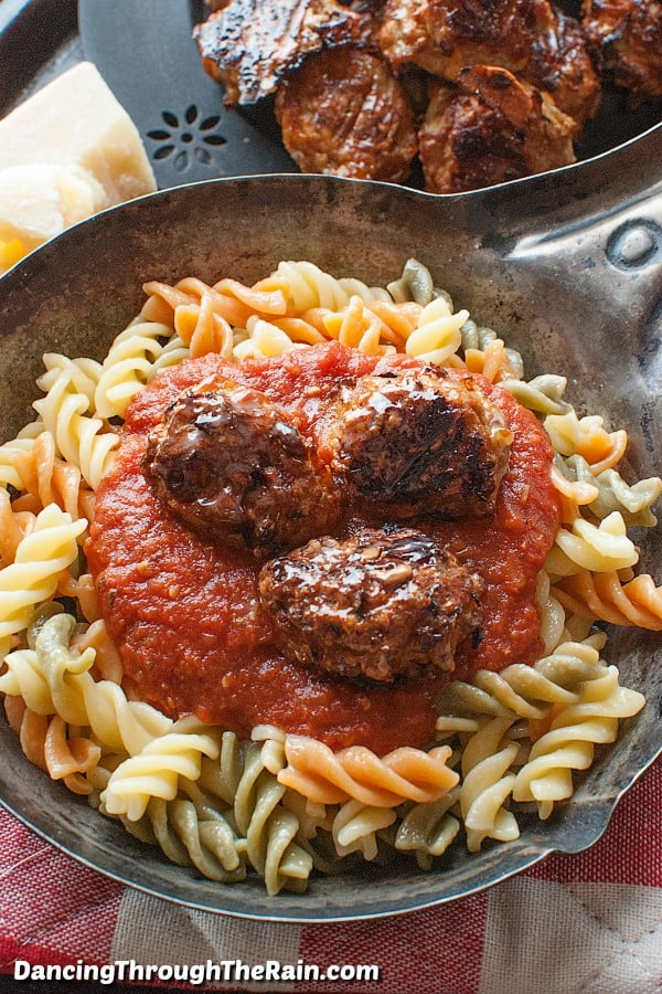 baked chicken meatballs on a plate of rotini pasta with red sauce.